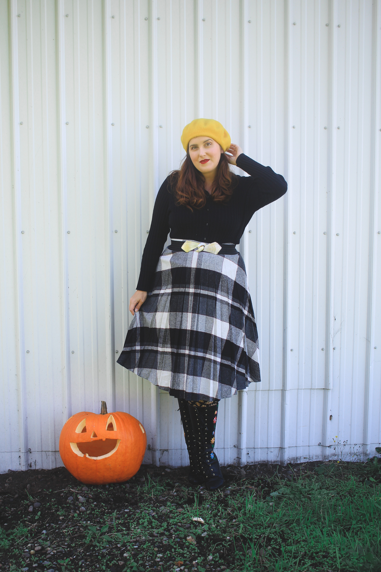 woman wearing a yellow beret and a plaid skirt