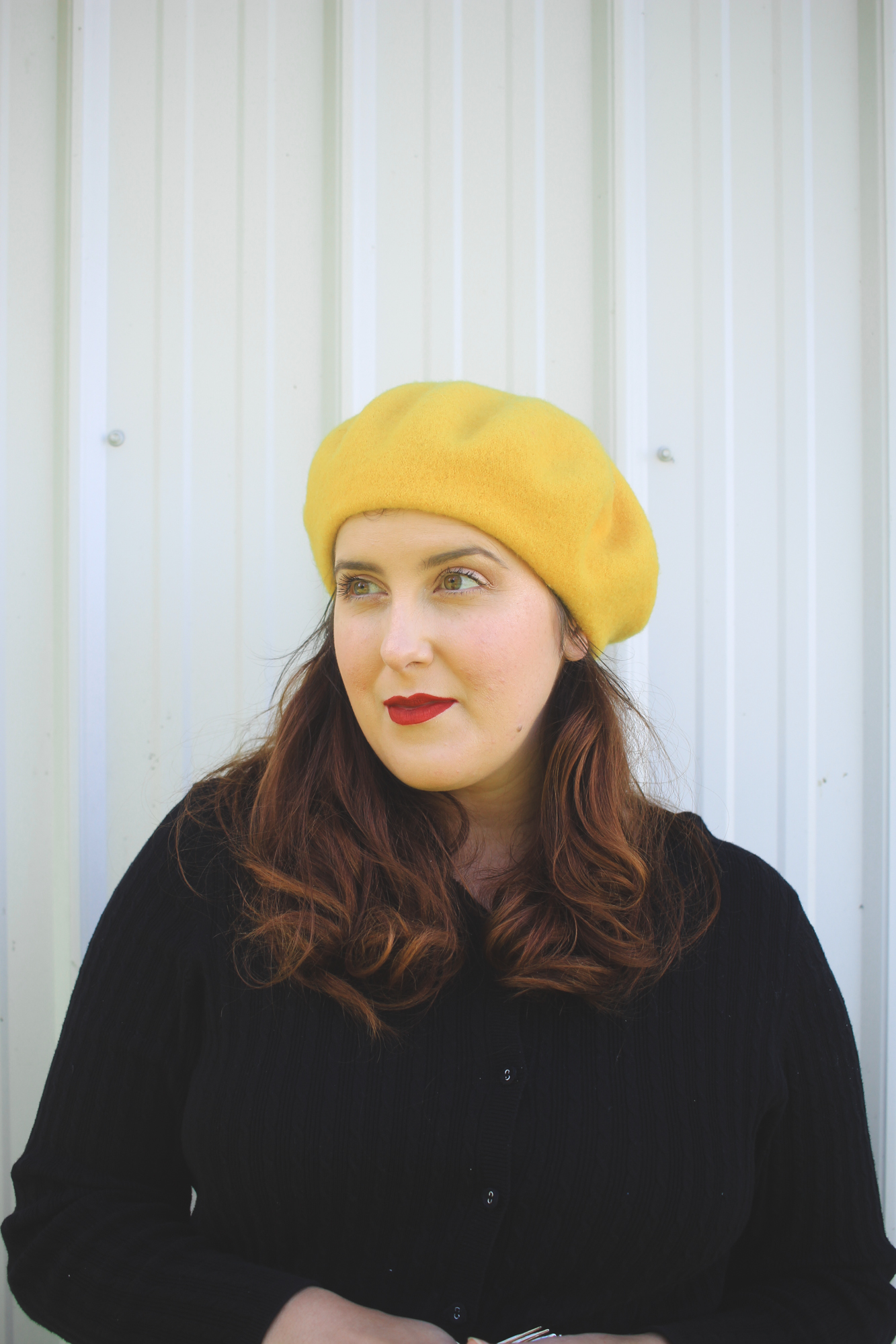 woman with curled hair wearing a yellow beret